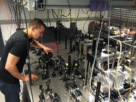 Paul Klimov, a graduate student in the Institute for Molecular Engineering, adjusts the intensity of a laser beam during an experiment