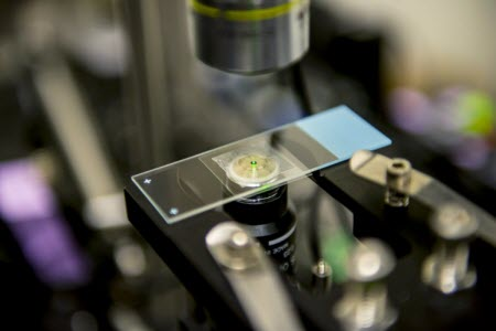 "As they are cooled by the laser, the nanocrystals developed by the UW team emit a reddish-green ""glow"" that can be seen by the naked eye"